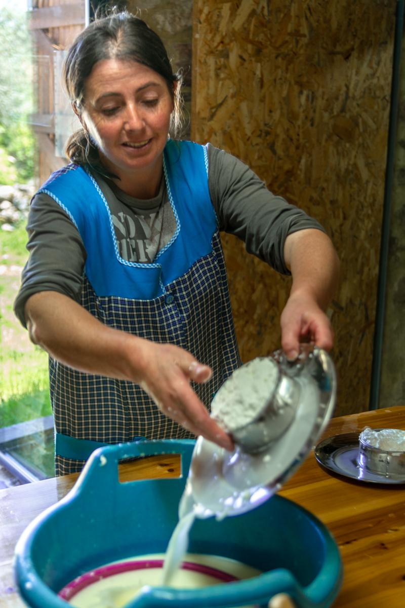 Fatima gießt den Käsebruch ab. Alles geeschieg in dem kleinen Ziegenstallt in Ferraria-de-São-Joã